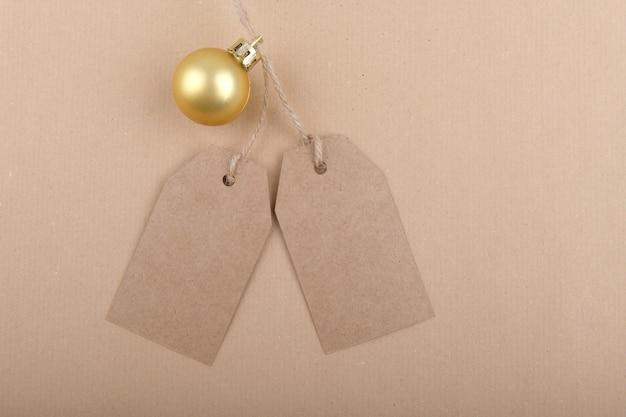 Twee labels van gerecycled kraftpapier voor verpakking, hangend aan een touw versierd met een gouden kerstbal