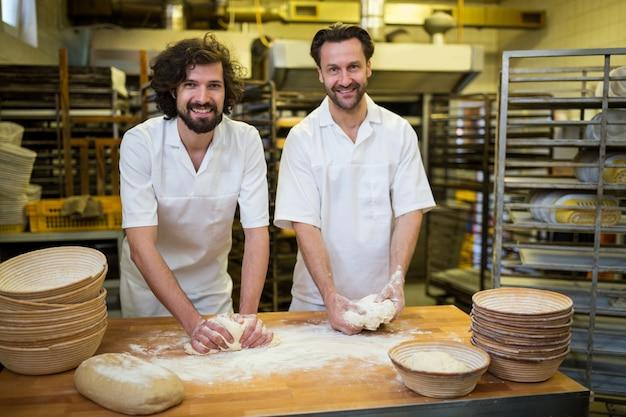 Twee lachende bakkers kneden van deeg