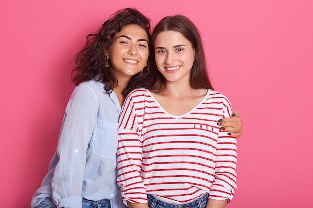 Twee lachende dames poseren met een charmante glimlach