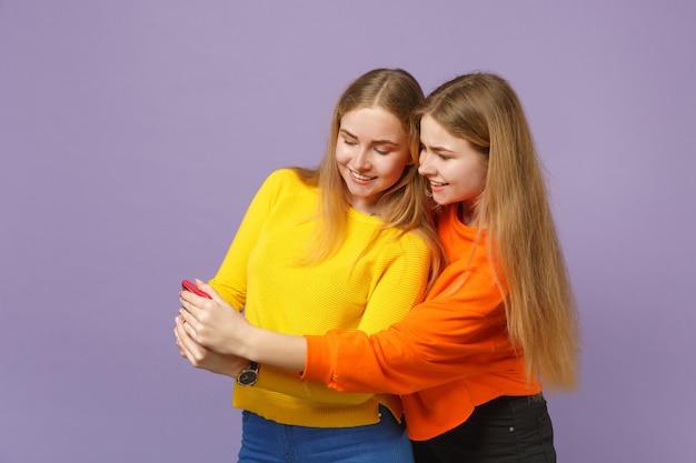 Twee lachende jonge blonde tweeling zusters meisjes in levendige kleding met behulp van mobiele telefoon sms-bericht te typen geïsoleerd op pastel violet blauwe muur. mensen familie levensstijl concept.