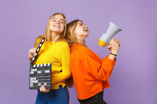 Twee lachende jonge blonde tweelingzusters meisjes houden klassieke zwarte film filmklapper, schreeuwen op megafoon geïsoleerd op violet blauwe muur. mensen familie levensstijl concept.