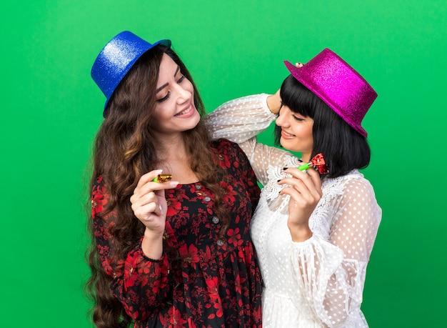 Twee lachende jonge feestmeisjes met een feestmuts die allebei een feesthoorn vasthouden en naar elkaar kijken, een elleboog op de schouder van haar vriend en hand op haar eigen hoofd geïsoleerd op een groene muur