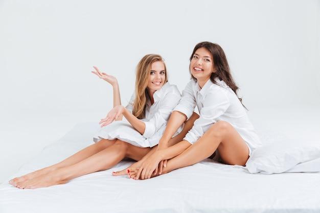 Twee lachende jonge vrouwen die shirts op bed dragen en naar de camera kijken