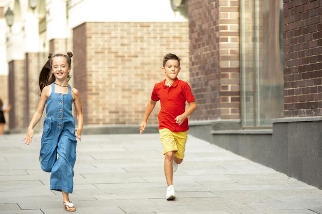 Twee lachende kinderen, jongen en meisje lopen samen in de stad, stad in zomerdag