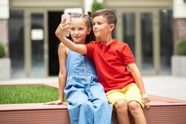 Twee lachende kinderen, jongen en meisje nemen samen selfie in de stad, stad in zomerdag