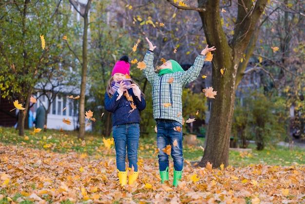 Twee lachende kinderen spelen buiten met esdoornbladeren