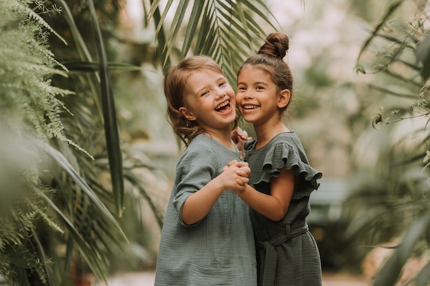 Twee lachende kleine meisjes die tot verschillende rassen behoren in linnen kleding, hand in hand en wandelend
