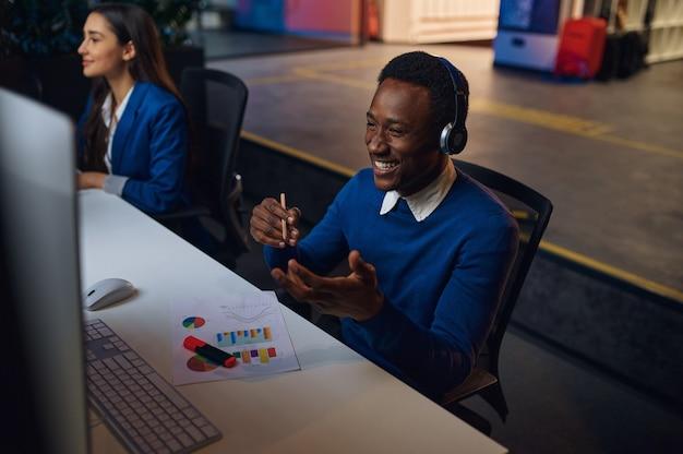 Twee lachende managers werken in nachtkantoor. vrolijke mannelijke en vrouwelijke werknemers, donker zakencentrum interieur, moderne werkplek