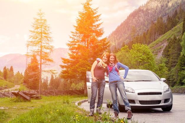 Twee lachende meisjes die met de auto reizen door de dolomieten, italië