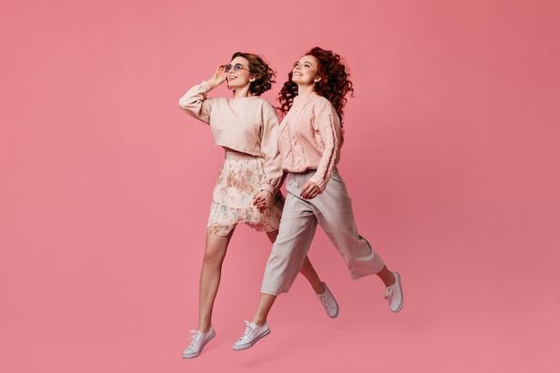 Twee lachende meisjes hand in hand. studio shot van vrouwelijke vrienden die op roze achtergrond lopen.