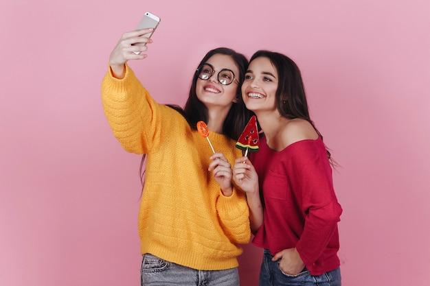 Twee lachende meisjes nemen selfie op hun telefoons poseren met lollies