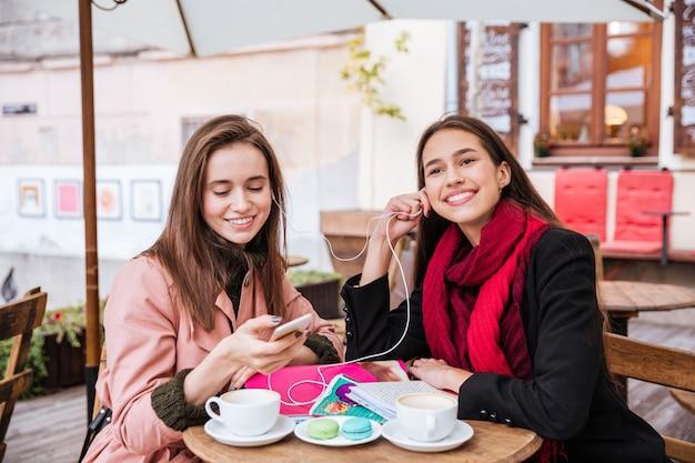 Twee lachende mooie jonge vrouwen met koptelefoon luisteren naar muziek van mobiele telefoon in openluchtcafé