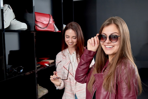 Twee lachende mooie meisjes die op modieuze moderne modieuze zonnebril proberen