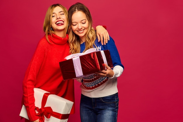 Twee lachende mooie vrouwen in stijlvolle truien met grote geschenkdozen