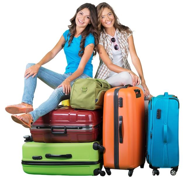 Twee lachende mooie vrouwen op stapel koffers op de achtergrond