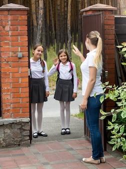 Twee lachende schoolmeisjes die naar school gaan en naar hun moeder zwaaien