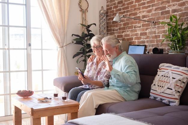 Twee lachende senior mensen in videogesprek met mobiele telefoon. thuis op de bank zitten