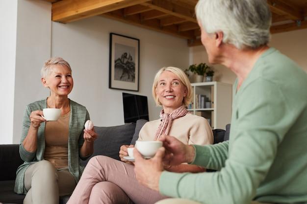 Twee lachende senior vrouwen thee drinken en praten met man zittend op de bank in de woonkamer