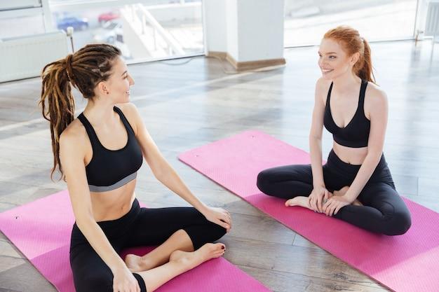 Twee lachende sportvrouwen die op roze matten zitten en praten na de training