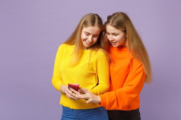 Twee lachende verbaasde jonge blonde tweelingzusters meisjes in levendige kleding met behulp van mobiele telefoon typen sms-bericht geïsoleerd op violet blauwe muur. mensen familie levensstijl concept.