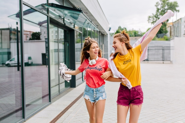 Twee lachende vrienden gaan winkelen in de zomerochtend en vertellen elkaar grappige verhalen