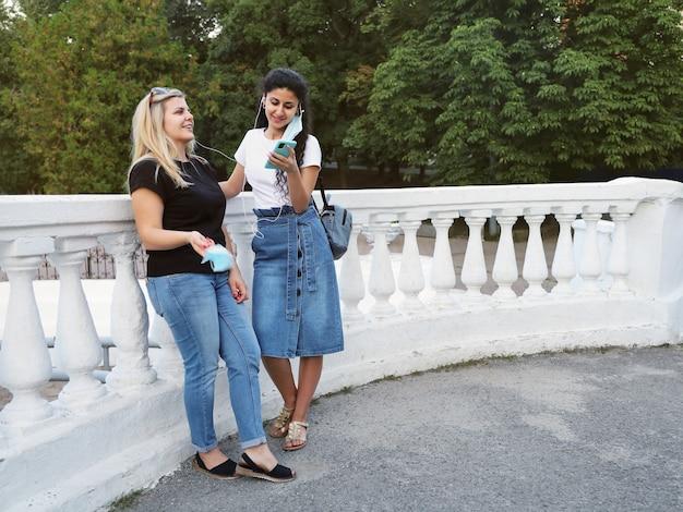 Twee lachende vriendinnen staan dicht in het park en luisteren naar muziek in dezelfde koptelefoon