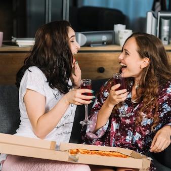 Twee lachende vrouwelijke vrienden met drankjes en pizza
