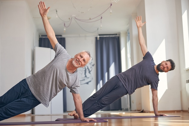 Twee lachende yogi's ondersteunen het gewicht van hun lichaam op één hand en een voet