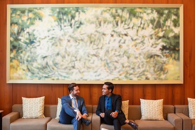 Twee lachende zakenmensen chatten in lounge