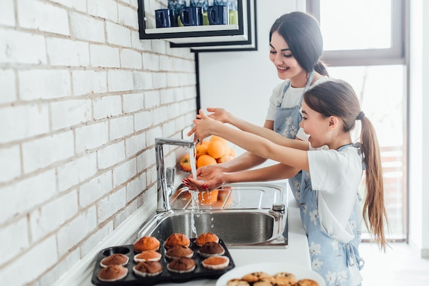 Twee lachende zussen die handen wassen in de keuken thuis