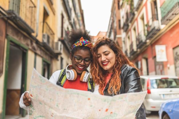Twee latijnse tienermeisjes die een kaart gebruiken en samen reizen.