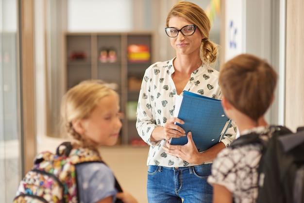 Twee leerlingen praten met een leraar