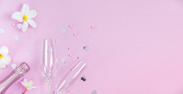 Twee lege champagneglazen en fles champagne met witte frangipanibloemen en kleine hartdecoratie op roze achtergrond