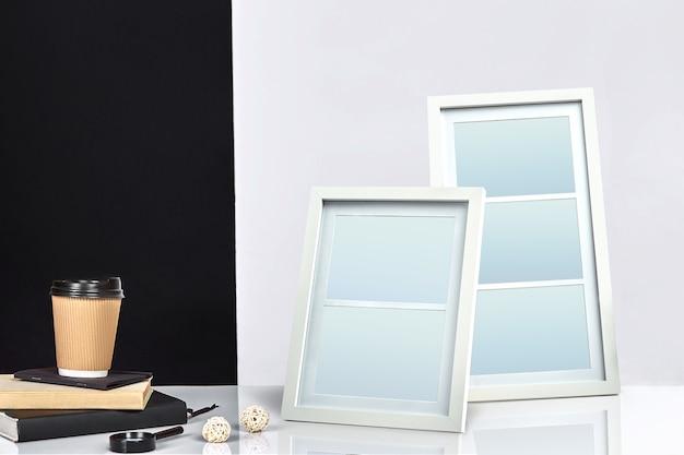 Twee lege frames, papieren kopje koffie op boeken en vergrootglas
