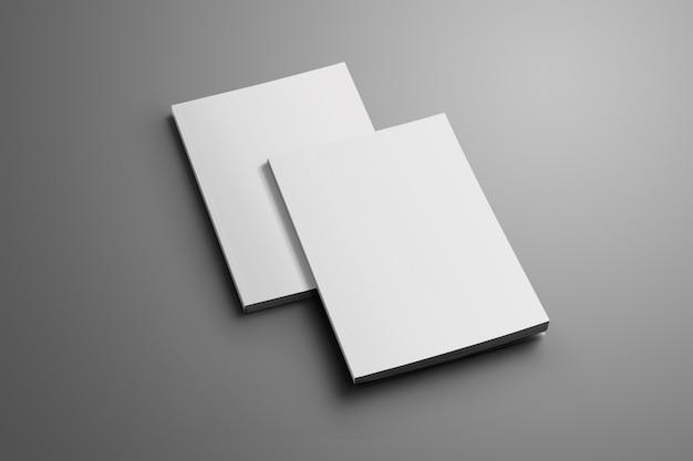 Twee lege gesloten a4, (a5) brochures met zachte schaduwen geïsoleerd op grijs oppervlak. een van de brochures ligt van de tweede brochure.