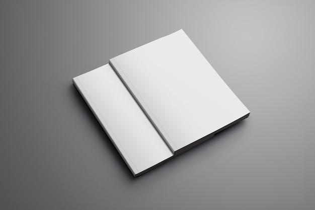 Twee lege gesloten a4, (a5) tijdschriften met zachte schaduwen geïsoleerd op grijs oppervlak. een van de brochures ligt van de tweede brochure.