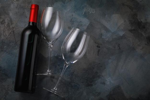 Twee lege glazen en een fles rode wijn op tafel