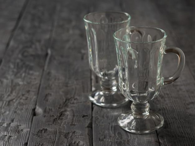 Twee lege koffieglazen op de houten tafel