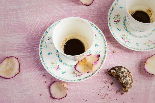 Twee lege koffiekopjes en rozenblaadjes.