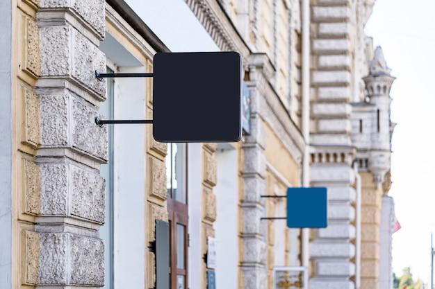 Twee lege mock-up ontwerp van café uithangbord buiten op gele muur