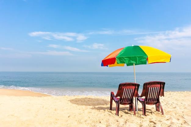 Twee lege stoelen onder een veelkleurige regenboogparaplu staan op een zandstrand tegen de achtergrond van een prachtige blauwe zee.