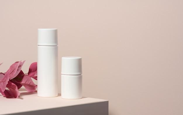 Twee lege witte plastic buizen voor cosmetica staan op een houten podium op een beige achtergrond met een schaduw. containers voor crème, shampoo, vloeibare stoffen. branding, sjabloon