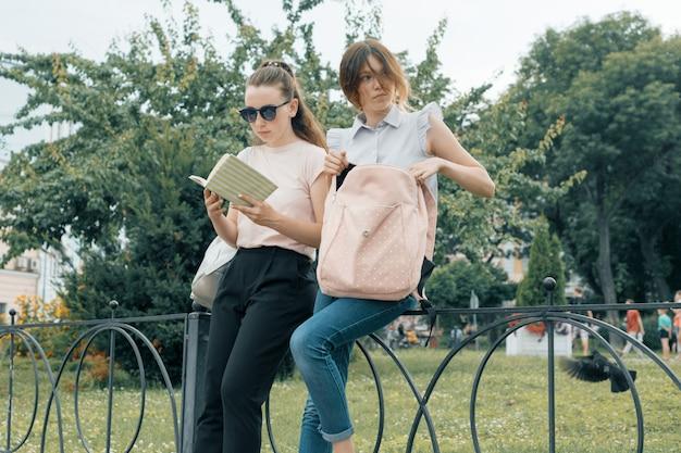 Twee lerende meisjesstudenten met rugzakken en handboeken openlucht in een park