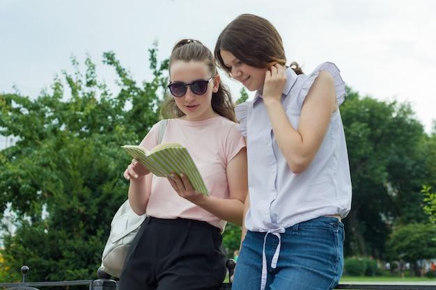 Twee lerende meisjesstudenten met rugzakken openlucht