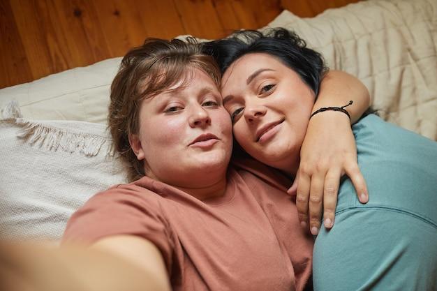 Twee lesbiennes die elkaar omhelzen en poseren voor de camera die ze een selfie-portret maken