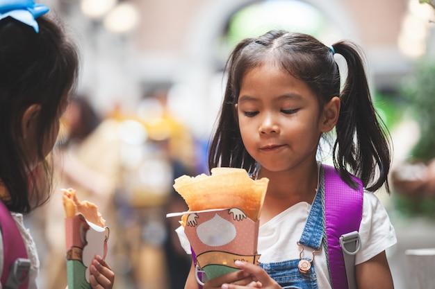 Twee leuke aziatische kindmeisjes die met rugzak pannekoek samen na school in de school eten