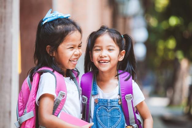 Twee leuke aziatische kindmeisjes die met schooltas een boek houden en samen in de school spreken
