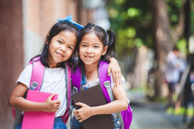 Twee leuke aziatische kindmeisjes die met schooltas een boek samen in de school houden