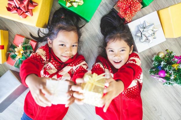 Twee leuke aziatische kindmeisjes die op de vloer bepalen en giftdozen in kerstmisviering geven