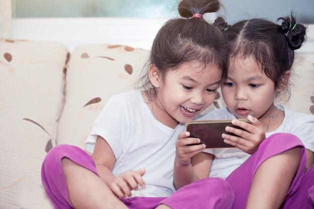Twee leuke aziatische kindmeisjes die pret hebben om spel in slimme telefoon samen in de ruimte te spelen